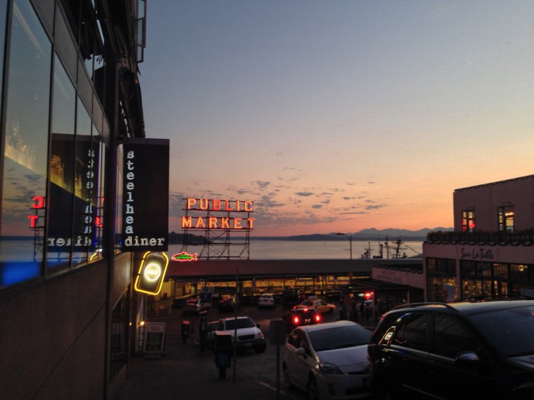 Pike Place Market with Puget Sound and the Olympic Mountains on the horizon.