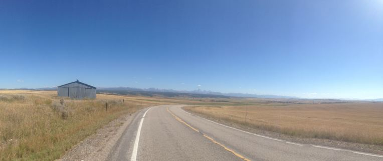 Tetons on the horizon around Mile 30. Vast stretches farm fields interrupted by pavement.